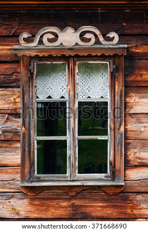 Rustic wooden house window with simple ornaments and curtain - stock photo