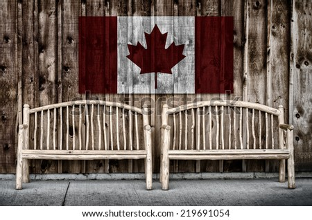 Rustic wooden log benches side by side against a wall of wooden siding with the flag of Canada imprinted above the benches.  Filtered for a retro, vintage look.  - stock photo