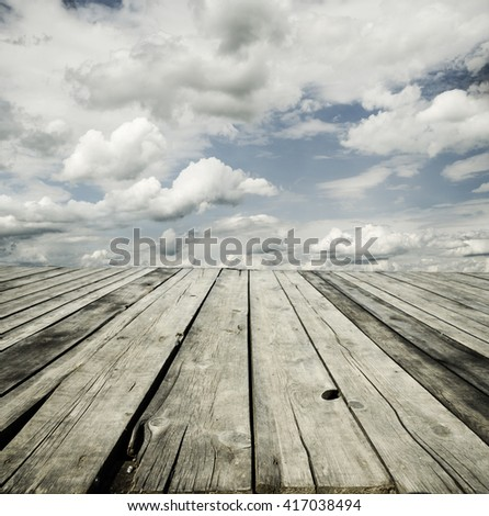 Rustic wooden planks and cloudy sky background design. - stock photo