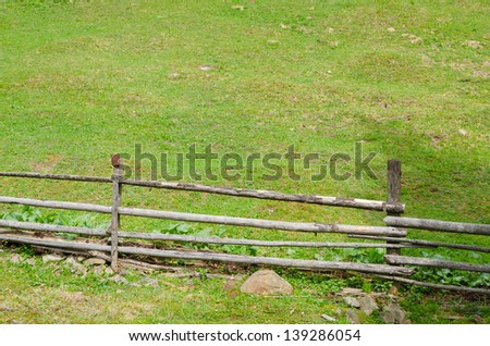 Rustic wooden pole and rail fence bordering on a lush rural pasture - stock photo