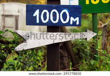 Rustic wooden road right direction arrow sign - stock photo