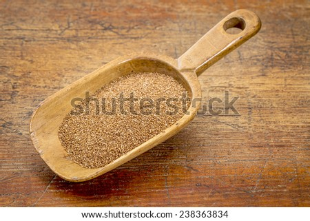 rustic wooden scoop of gluten free teff grain against grunge wood background - stock photo