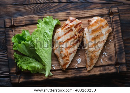 Rustic wooden serving board with grilled chicken breast filet - stock photo