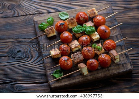 Rustic wooden serving board with tomatoes and cheese skewers