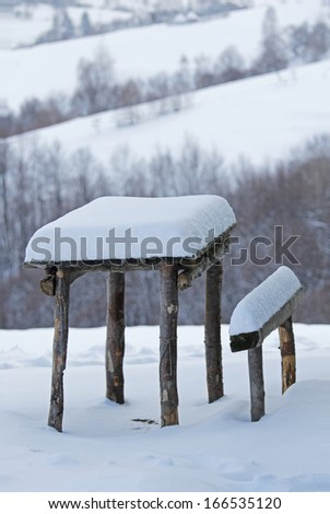 Rustic wooden table and chair under the snow - stock photo