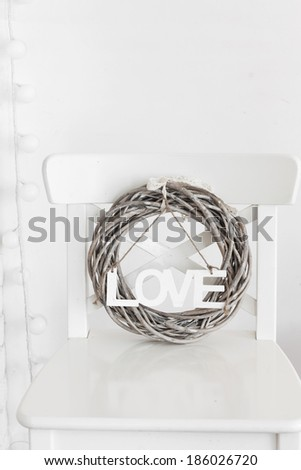 Rustic wreath with wooden letters on a white shabby chic chair near the wall - stock photo