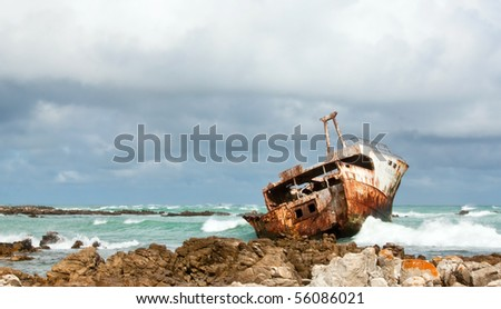 Rusting broken Shipwreck lying on the rocks with green ocean and cloudy sky