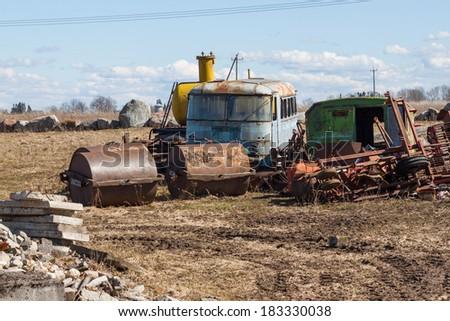 rusting farm machinery in a farm field - stock photo