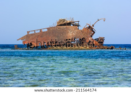 Rusting metal shipwreck on a tropical coral reef - stock photo