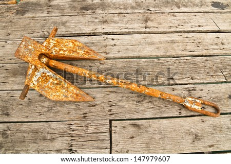 Rusty anchor on old wood plank