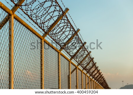 rusty barbed wire fence in sunny day - stock photo