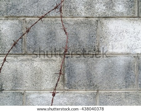 Rusty barbed wire on concrete block wall texture background - stock photo