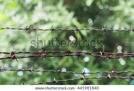 Rusty barbed wire on nature background, selective focus - stock photo