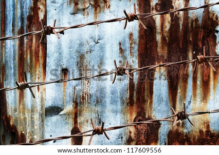 Rusty barbed wire on rust wall