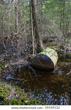 Rusty barrel dumped in swampy forest