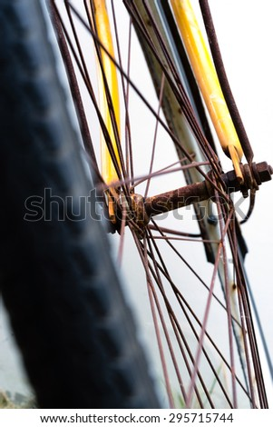 Rusty bicycle front wheel include spokes, front fork, tire, against on background - stock photo