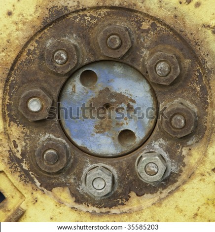 Rusty bolts in yellow wheel of tractor
