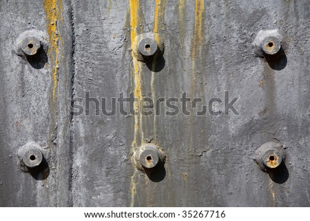 Rusty bolts on painted metal plate