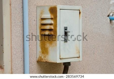 Rusty breaker box on old dirty wall. - stock photo