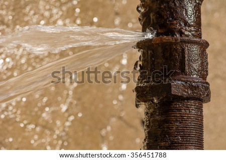 Rusty burst pipe spraying water after freezing in winter. - stock photo
