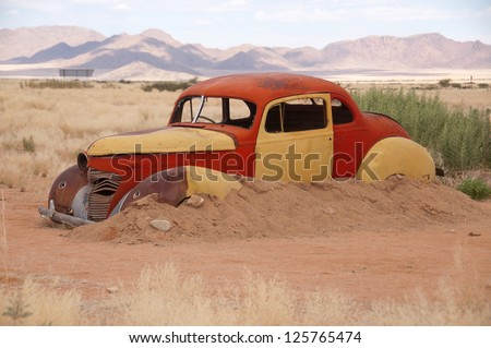 rusty car in the desert - stock photo