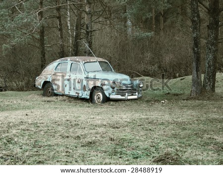 rusty car in the forest