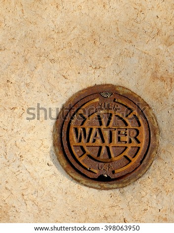 Rusty cast iron manhole cover as used in a public street. Provide access for shutoff valves and sewer cleanout and manufactured by many different companies. - stock photo
