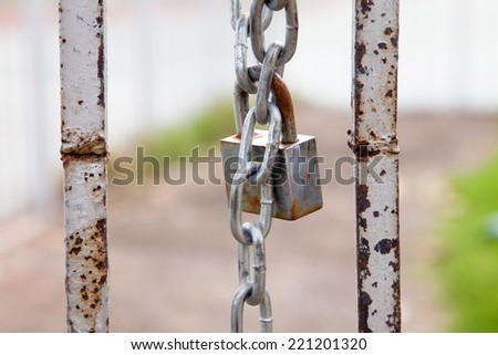 rusty chain and master key locked on grunge iron gate - stock photo