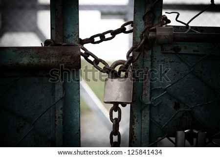 Rusty chain and padlock around a fence - stock photo