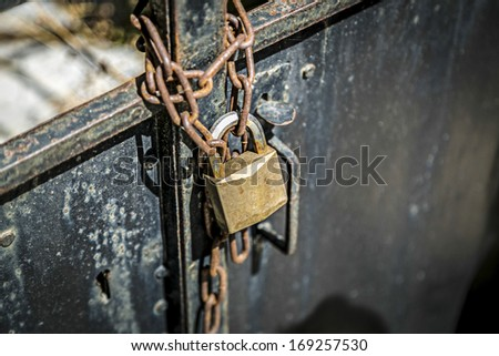 rusty chain on a metal door with  padlock. - stock photo
