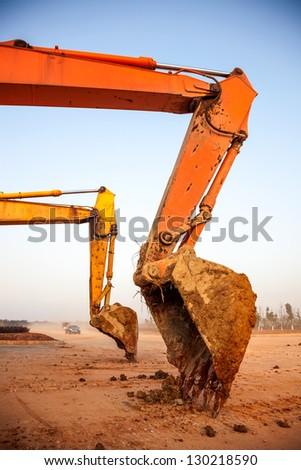 rusty claw of a bulldozer under blue sky - stock photo