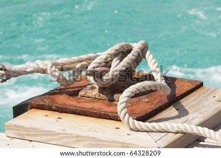 Rusty cleat with ship's mooring line tied securely. Horizontal shot.