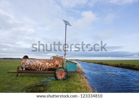 Rusty container, providing drinking water for cattle, a solar panel providing electricity for a pump - stock photo