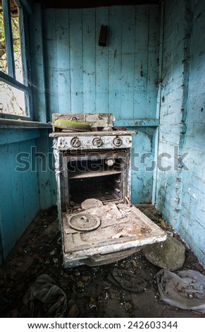 rusty cooker in wooden cottage in small abandoned village called Stechanka, Chernobyl Nuclear Power Plant Zone of Alienation, Ukraine - stock photo