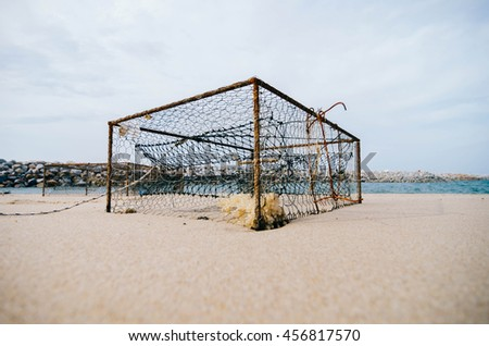 rusty crab pots on the sandy beach over blurred water break background.focus in the middle.shallow depth of field.color toning effect - stock photo
