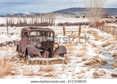 Rusty, dilapidated, abandoned vehicle in a field in rural America on a winter day - stock photo