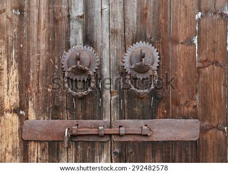 Rusty door knobs and bolt on an old wooden door - stock photo