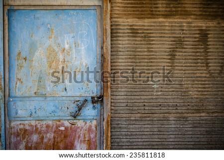Rusty door texture of an old garage door and wall - stock photo