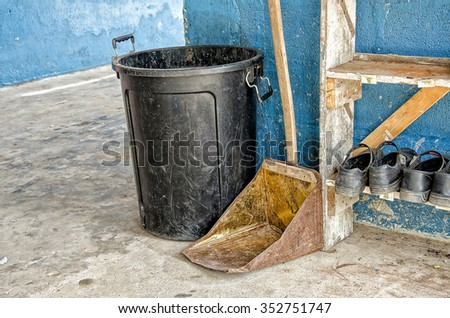 Rusty dustpan.Trash black with rust dustpan at cement wall background.