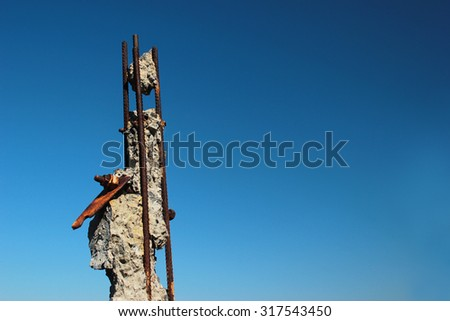 Rusty ends of steel reinforcing bars sticking out of demolished concrete pole on blue sky background - stock photo