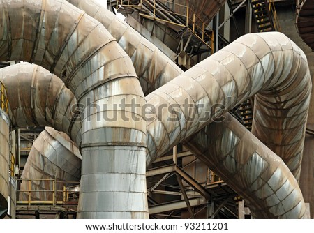 Rusty exhaust pipe of an industrial manufacturing pipe meandering and curving around in an intricate pattern. - stock photo