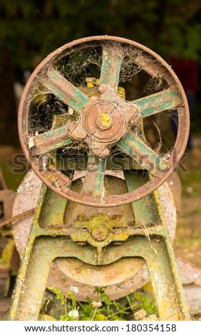 Rusty farm equipment or machinery abandoned in forest with flywheel and motor pulley - stock photo