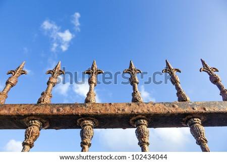 rusty fence under blue sky - stock photo