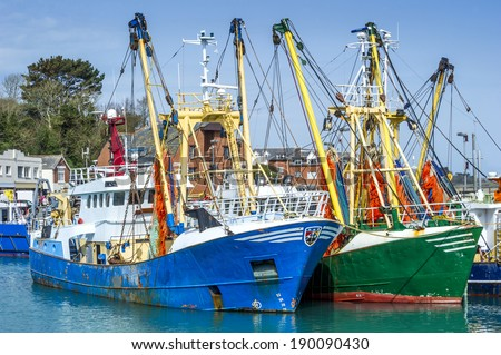 Rusty fishing trawlers moored in the port of a small fishing village - stock photo