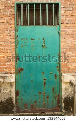 Rusty green metal door on orange brick wall - stock photo