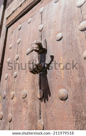 rusty hand shaped knocker in an old wooden door - stock photo