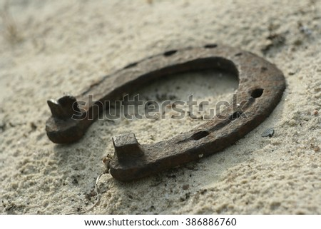 Rusty horseshoe on a sand background - rustic scene in a country style. Old iron Horseshoe - good luck symbol and mascot of well-being in a village house in Western culture. - stock photo