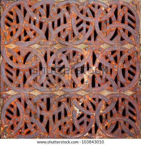 Rusty iron Celtic design storm Grating - stock photo