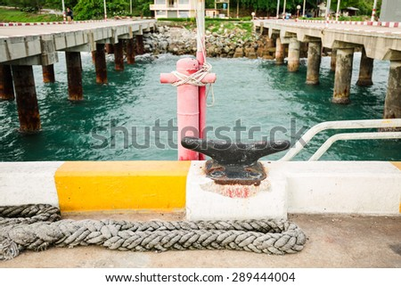 Rusty iron mooring mast and old rope on big port - stock photo