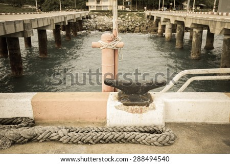 Rusty iron mooring mast and old rope on big port in vintage tone - stock photo